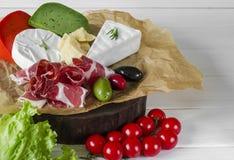 Blanda ost och kött på vit bakgrund på träbräde med druvor, honung, muttrar, tomater och basilika Top beskådar arkivbilder