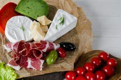 Blanda ost och kött på vit bakgrund på träbräde med druvor, honung, muttrar, tomater och basilika Top beskådar arkivfoto