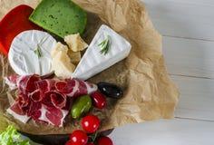 Blanda ost och kött på vit bakgrund på träbräde med druvor, honung, muttrar, tomater och basilika Top beskådar fotografering för bildbyråer