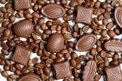 Blandad chokladgodis på bakgrunden av isolaen för kaffebönor royaltyfri bild