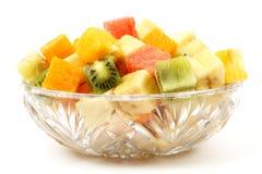 Blandad frukt h?gg av i kuber p? en platta p? vit bakgrund fotografering för bildbyråer