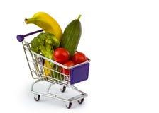 Blandad frukt och grönsaker i en mini- shoppingvagn som isoleras på Arkivbild