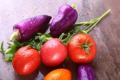 Blandad grönsak med purpurfärgade exotiska färgspanska peppar och tomater på stenbakgrund Royaltyfria Bilder