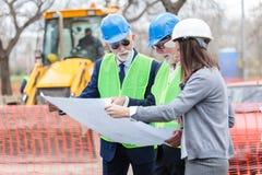 Blandad grupp av arkitekter och affärspartners som diskuterar projektdetaljer på en konstruktionsplats royaltyfria foton