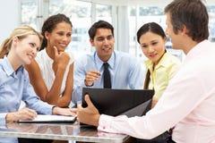 Blandad grupp i affärsmöte arkivbild