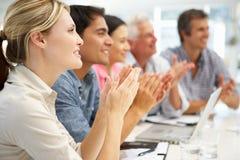 Blandad grupp som applåderar i affärsmöte