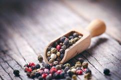 Blandad hel peppar på en träskopa Naturlig gammal bakgrund Begrepp av mat, krydda Royaltyfri Bild