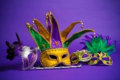 Blandad Mardi Gras eller Carnivale maskering på en purpurfärgad bakgrund arkivbild