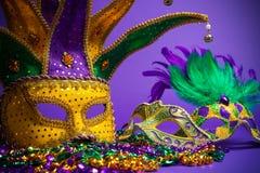 Blandad Mardi Gras eller Carnivale maskering på en purpurfärgad bakgrund royaltyfri bild