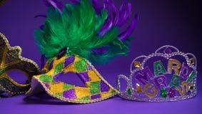 Blandad Mardi Gras eller Carnivale maskering på en purpurfärgad bakgrund Arkivfoton