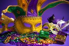 Blandad Mardi Gras eller Carnivale maskering på en purpurfärgad bakgrund arkivfoto