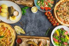Blandad matuppsättning med kopieringsutrymme Grillade grisköttstöd, pizza, sallad, fisk och korvar med stekte potatisar Smaklig d arkivfoto