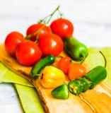 Blandad peppar och tomater på träbakgrund Arkivbilder