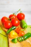 Blandad peppar och tomater på träbakgrund Arkivbild