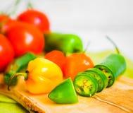 Blandad peppar och tomater på träbakgrund Arkivfoto