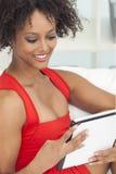 Blandad Raceafrikansk amerikanflicka som använder Tabletdatoren Arkivfoto