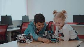 Blandad ras- grupp av idérika ungar som arbetar på techprojektet på skola Studentpojke- och flickalek och att lära till lager videofilmer