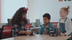Blandad ras- grupp av idérika ungar som arbetar på techprojektet på skola Studentpojken och flickor spelar och lär till stock video