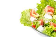 Blandad salat i en glass bunke som isoleras på vit. Arkivbild
