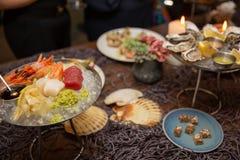 Blandad skivad fisksashimi och räkor på is i svart bunke Sashimi Salmon Tuna Hamachi Prawn och bränningstillhetuppsättning, rå fi arkivbilder