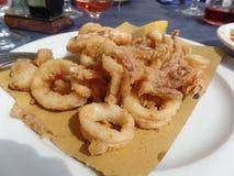 Blandad stekt skaldjur tjänade som på en utomhus- terrass i sydliga Italien royaltyfri fotografi