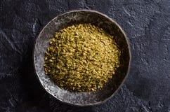 Blandad östlig krydda - som är zaatar eller som är zatar i metalltappningbunke på mörk stenbakgrund Selektivt fokusera Royaltyfri Bild