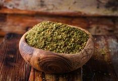 Blandad östlig krydda - som är zaatar eller som är zatar i tappningbunke på träbakgrund Selektivt fokusera Fotografering för Bildbyråer