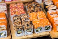 Blandad sushi och rullar på det wood brädet i mörkt ljus royaltyfri bild
