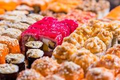 Blandad sushi och rullar på det wood brädet i mörkt ljus arkivbild