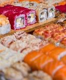 Blandad sushi och rullar på det wood brädet i mörkt ljus arkivfoton