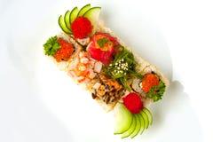 Blandad sushirulle med sesamfrö, gurka, tobiko, chukasallad, ål, tonfisk, räka, lax Arkivbild