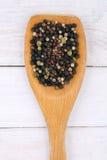 Blandad torkad kryddig peppar i en träsked på tabellen Royaltyfria Foton
