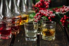 Blandade alkoholiserade fruktjuice i exponeringsglas och karaffer med julpynt Royaltyfri Fotografi
