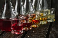 Blandade alkoholiserade fruktjuice i exponeringsglas och karaffer med julpynt Royaltyfri Foto