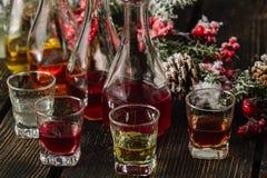 Blandade alkoholiserade fruktjuice i exponeringsglas och karaffer med julpynt Arkivbilder