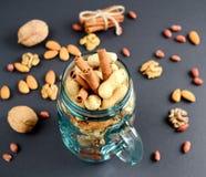 Blandade blandade muttrar i en glass krus, jordnötter, mandlar, valnötter och sesamfrö Arkivbild