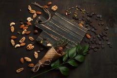 Blandade blandade muttrar och choklad på en träskärbräda Nära övre, selektivt fokuserar Arkivbilder