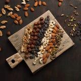Blandade blandade muttrar och choklad på träbakgrund Royaltyfri Fotografi
