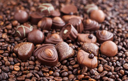 Blandade chokladbrända mandlar på bakgrund för kaffebönor Arkivbild