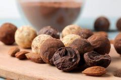 blandade choklader Godisbollar av olika typer av choklad på ett träbräde på en blå trätabell mandel och kakao arkivfoto