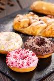 Blandade donuts med glasade rosa färger, choklad glaserade och stänk Arkivfoto