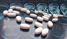 Blandade färgrika farmaceutiska medicinpiller och minnestavlor på bakgrund för magnetiskt huvud och för hjärnresonansbildläsning arkivfoto