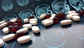 Blandade färgrika farmaceutiska medicinpiller och minnestavlor på bakgrund för magnetiskt huvud och för hjärnresonansbildläsning royaltyfri bild