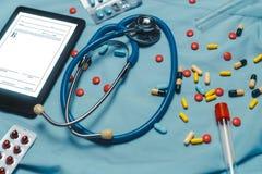 Blandade farmaceutiska medicinpreventivpillerar, minnestavlor och kapslar över blå bakgrund Arkivbild
