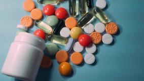 Blandade farmaceutiska medicinpreventivpillerar, minnestavlor och kapslar och flaska på blå bakgrund stock video