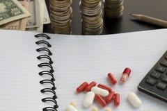 Blandade farmaceutiska piller eller kapslar, räknemaskin på den vita tomma fodrade notepaden royaltyfria foton
