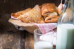 blandade frukostbakelser och mjölkar arkivfoto