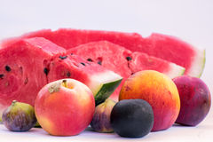 Blandade frukter, skivor av vattenmelon, persika, fikonträd, plommon, äpple På en vit bakgrund Fotografering för Bildbyråer