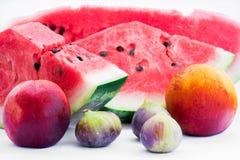 Blandade frukter, skivor av vattenmelon, persika, fikonträd, plommon, äpple På en vit bakgrund Arkivfoton