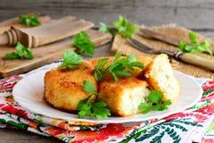 Blandade grönsakkotletter med äggfyllning på en vit platta Stekte blomkålpotatiskotletter med äggfyllning Hemlagad vegetarian arkivfoto